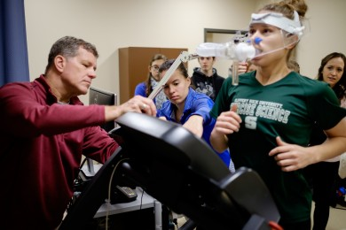 HES professor Pete Brubaker teaches first-year graduate students in the cardiovascular lab. Natalie DiCicco, in green, undergoes a cardio test.