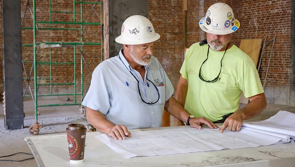 Jim Parham (left), superintendent on the Reynolds Gym transformation project, looks at blueprints.