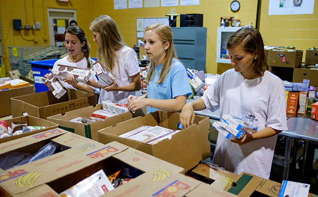 Students pack food at a food pantry