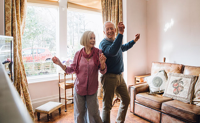 An older couple dances in their home.
