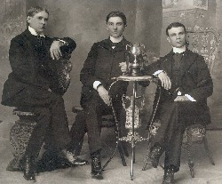 1899 Debaters pose with The Cup won in a five year series debate with Trinity (Duke) Pictured (L-R) Wayland Cooke, Oscar Powers, Archer Dunning