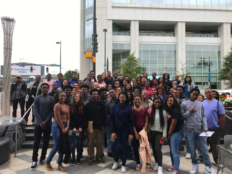 A large group of College LAUNCH students smile for a picture on a city street.