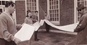 Football coach Bill Tate, at left; athletics director Gene Hooks ('50), at rear; director of communications Russell Brantley ('45), at right; and two unidentified students unroll the scroll on the Reynolda Hall patio.