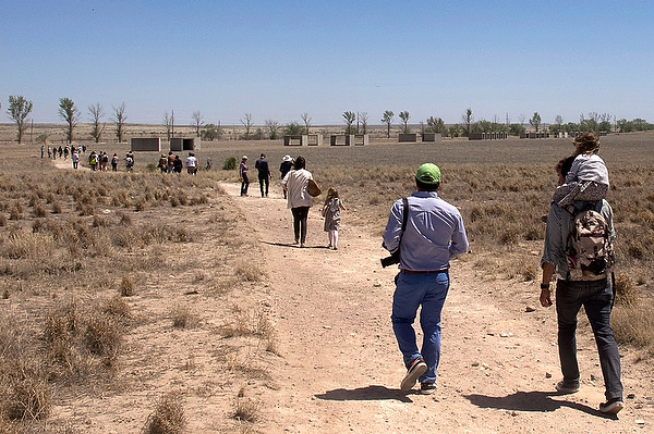 Visitors from around the world view the 15 concrete works that run along the border of Chinati's property.