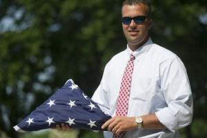 Jay holding folded flag